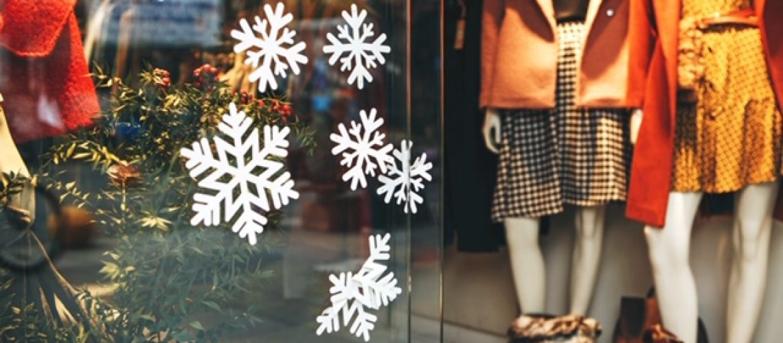 Showcase of a fashion store decorated with snowflakes for Christmas or New Year. In the background are mannequins. Sale season.